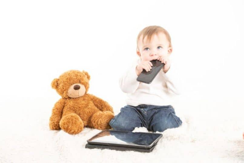 un nino pequeno con un celular y tablet
