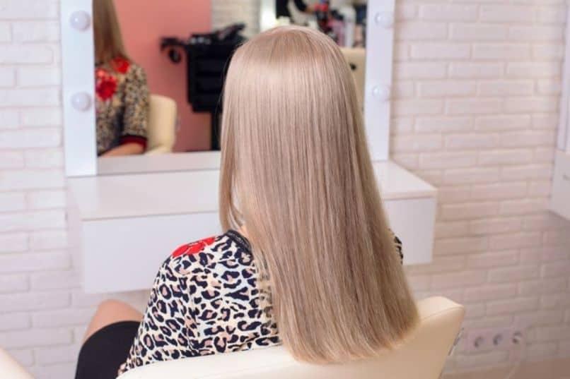 chica mostrando resultado de su cabello rubio