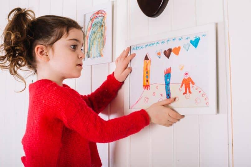 nina colgando un cuadro en su pared