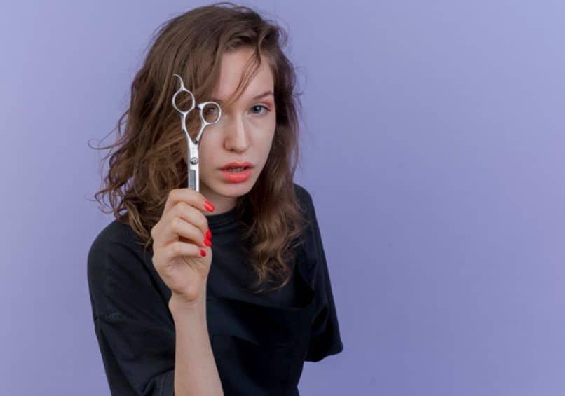 chica con tijeras en las manos para raparse el pelo y le quede bien