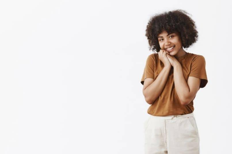 chica joven feliz de pie con pelo corto rizado afro