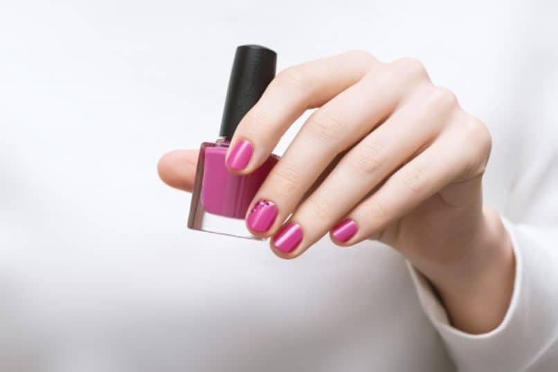 mano femenina sostiene botella de esmalte color de moda para unas segun tono de piel