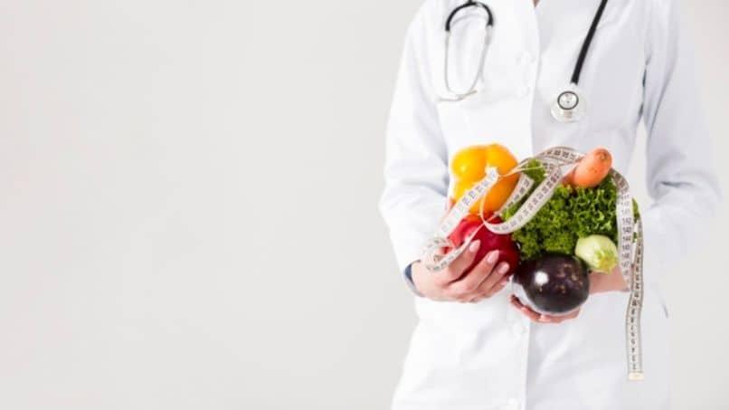 un medico con frutas en las manos para una dieta
