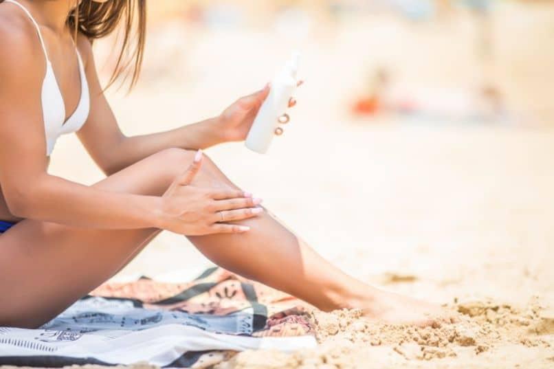 mujer aplicando protector solar en su pierna en la playa