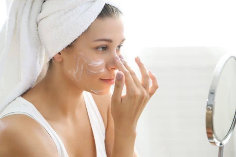 hermosa chica que aplica cremas para cuidar la piel de su rostro