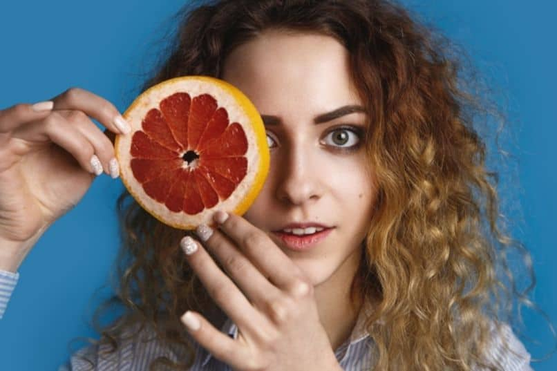 chica sostiene una fruta que contiene vitamina c
