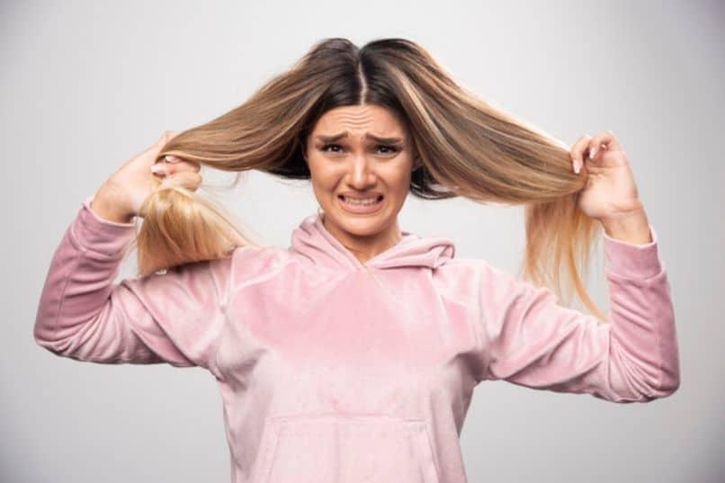 chica se agarra el pelo y esta nerviosa para raparse el pelo